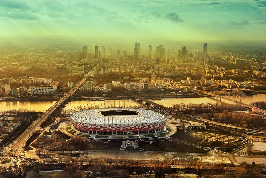 Fotografia Warszawy z lotu ptaka, stadion narodowy na pierwszym planie, w tle centrum
